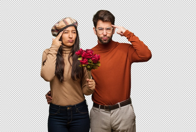 Young couple in valentines day doing a concentration gesture