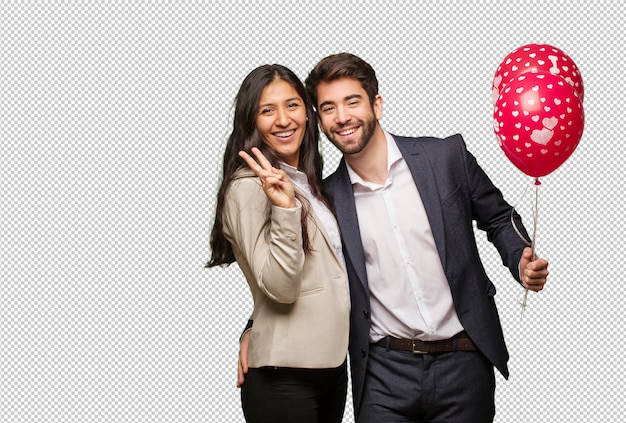 Young couple in valentines day doing a gesture of victory