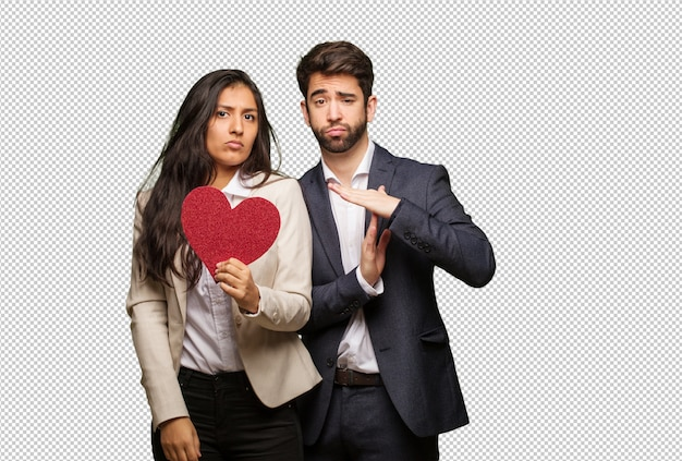 Young couple in valentines day doing a timeout gesture