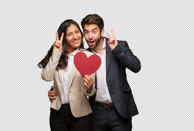 Young couple in valentines day fun and happy doing a gesture of victory