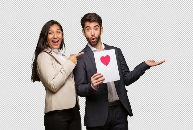Young couple in valentines day holding something on palm hand