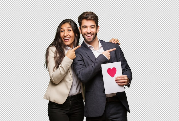 Young couple in valentines day pointing to the side with finger