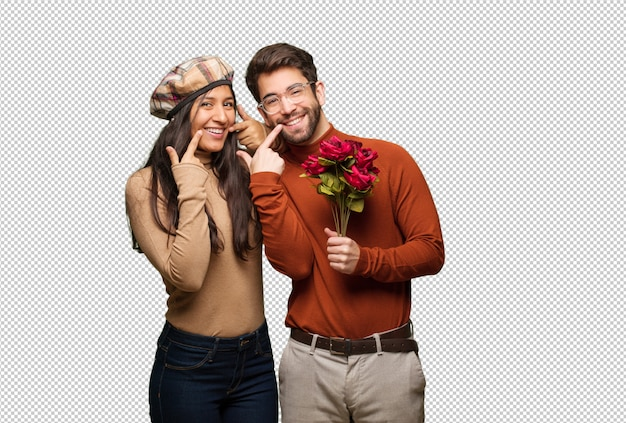 Young couple in valentines day smiles, pointing mouth