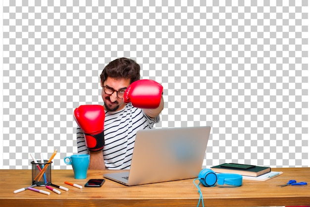 Young crazy graphic designer on a desk with a laptop and wearing boxing gloves