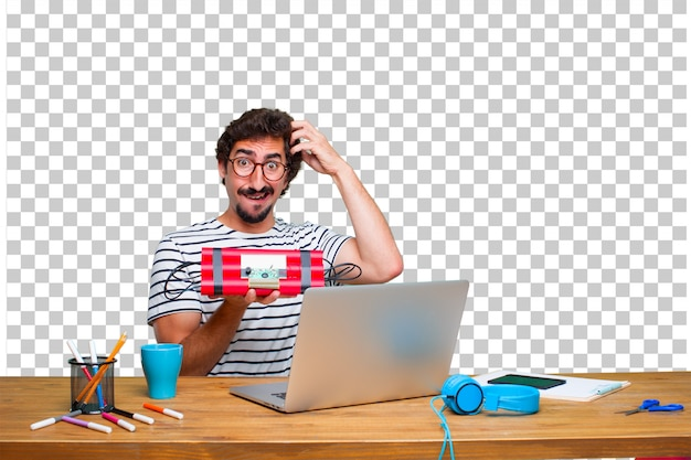 Young crazy graphic designer on a desk with a laptop and with a dynamite bomb