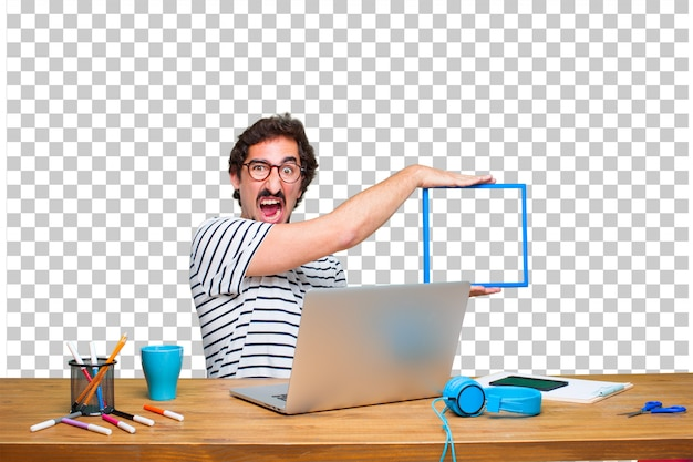 Young crazy graphic designer on a desk with a laptop and with a frame