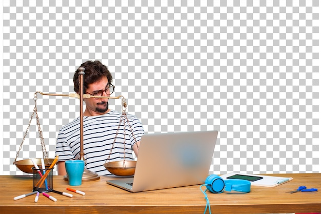 Young crazy graphic designer on a desk with a laptop and with a justice balance or scale
