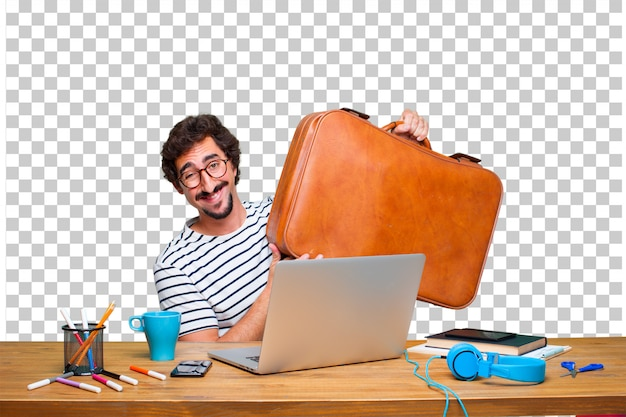 Young crazy graphic designer on a desk with a laptop and with a leather case luggage