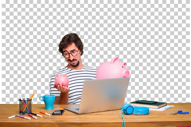 Young crazy graphic designer on a desk with a laptop and with a piggy bank