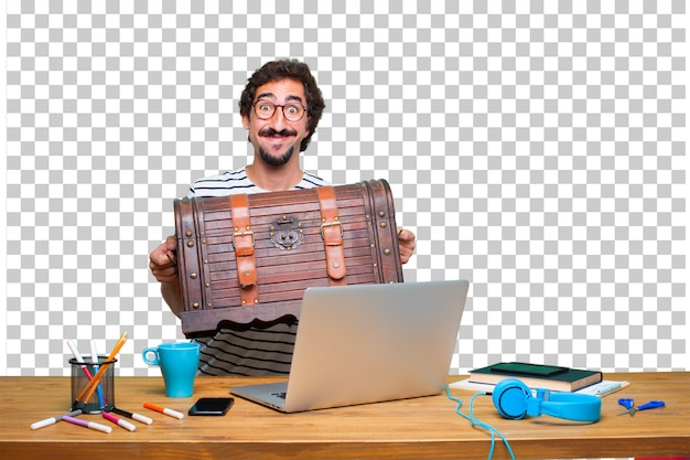Young crazy graphic designer on a desk with a laptop and with a pirate chest