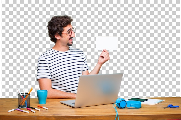 Young crazy graphic designer on a desk with a laptop and with a placard