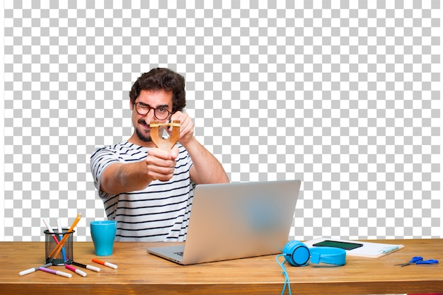 Young crazy graphic designer on a desk with a laptop and with a slingshot