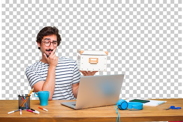 Young crazy graphic designer on a desk with a laptop and with a vintage box