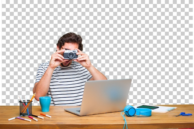 Young crazy graphic designer on a desk with a laptop and with a vintage camera