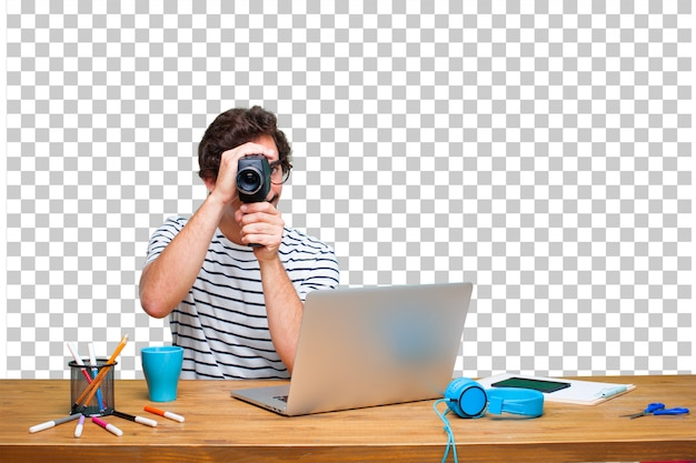 Young crazy graphic designer on a desk with a laptop and with a vintage cinema camera