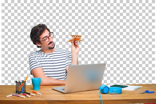 Young crazy graphic designer on a desk with a laptop and with a wooden plane
