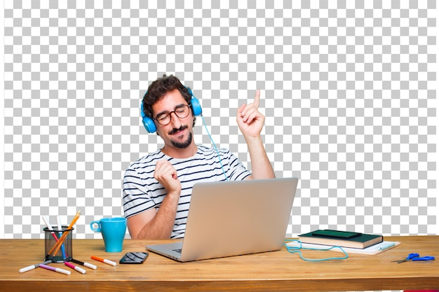 ノートパソコンを机の上にヘッドフォンで音楽を聴く若いクレイジーグラフィックデザイナー