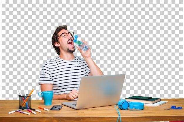 ノートパソコンと水のボトルを机の上の若いクレイジーグラフィックデザイナー