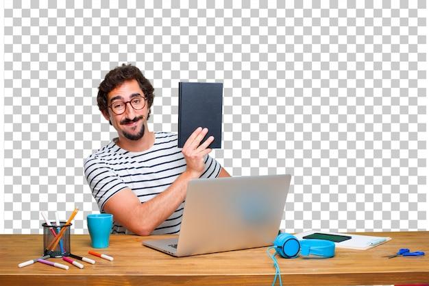Молодой сумасшедший графический дизайнер на столе с ноутбуком и с книгой