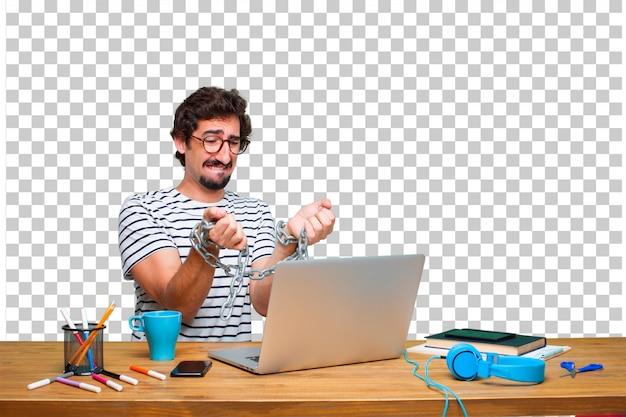 ノートパソコンとチェーン付きの机の上の若い狂気のグラフィックデザイナー。自由の概念