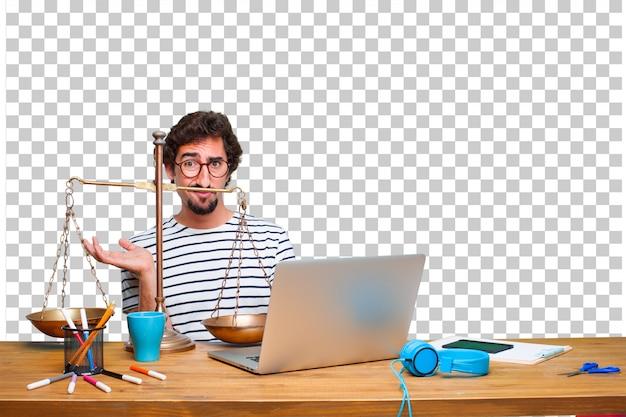 Молодой сумасшедший графический дизайнер на столе с ноутбуком и с справедливым балансом или масштабом