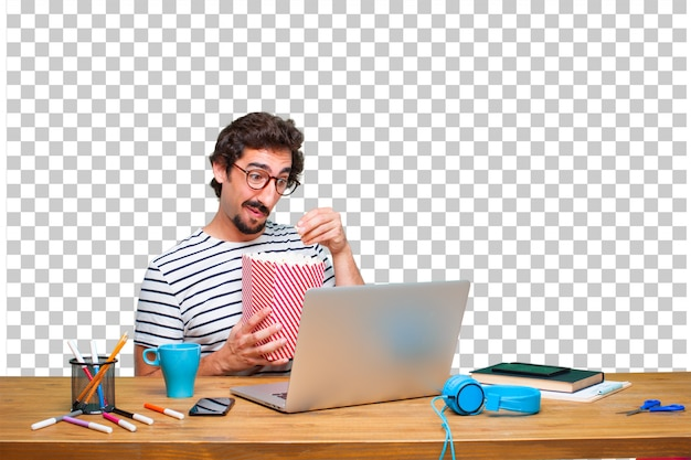 ラップトップとポップコーンバケツを机の上の若いクレイジーグラフィックデザイナー