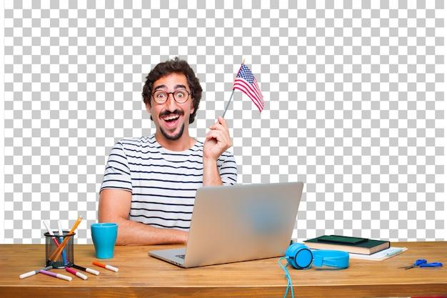 Молодой сумасшедший графический дизайнер на столе с ноутбуком и с флагом сша