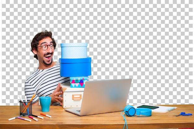 Молодой сумасшедший графический дизайнер на столе с ноутбуком и концепцией подарочной коробки