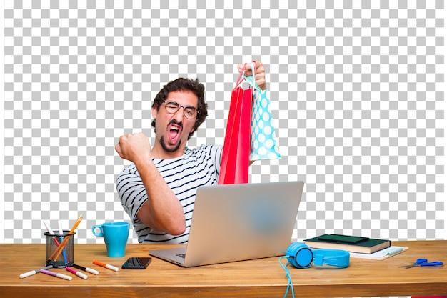 ラップトップと買い物袋を机の上の若い狂気のグラフィックデザイナー