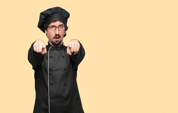 Young crazy man as a chef looking angry and surprised, shouting and pointing forward, towards you