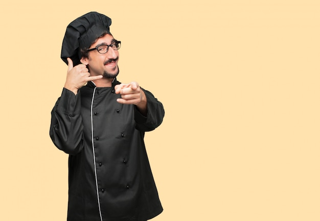 Young crazy man as a chef making a phone call gesture or sign, with a proud, happy, satisfied look