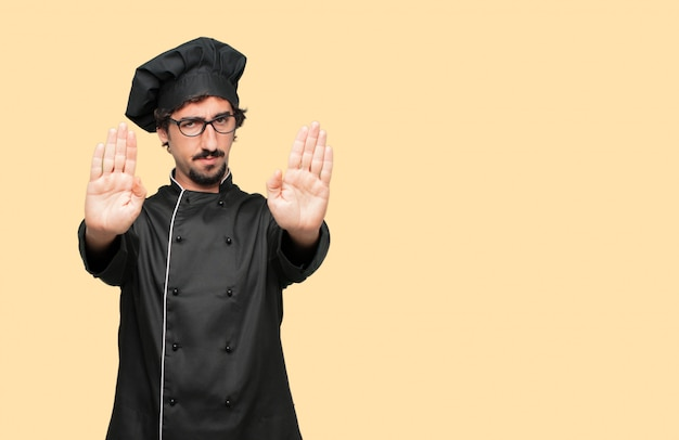 Young crazy man as a chef signaling stop with both palms of hands facing forward