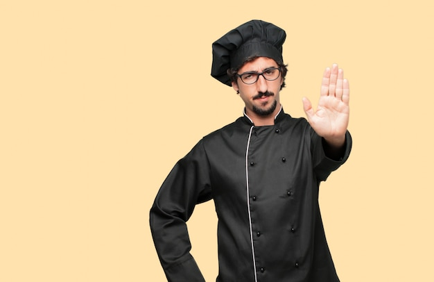Young crazy man as a chef signaling stop with the palm of hand facing forward