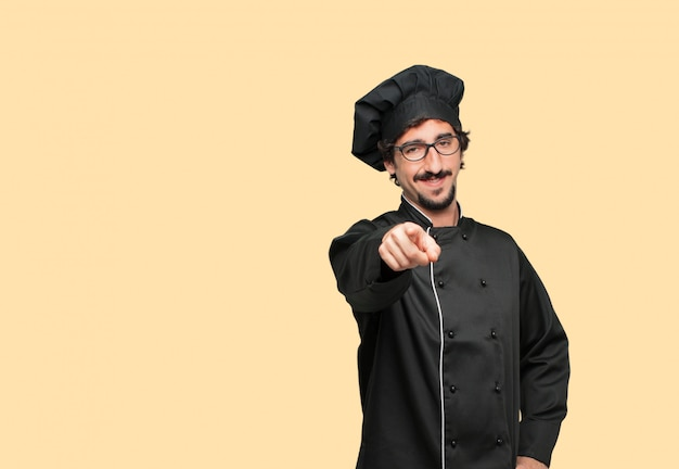 Young crazy man as a chef smiling happily and pointing forward, choosing you.
