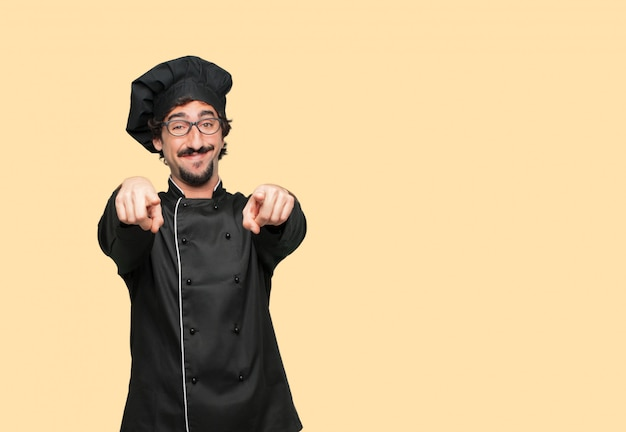 Young crazy man as a chef smiling happily and pointing forward with both hands, choosing you.