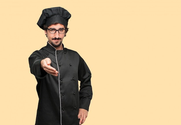 Young crazy man as a chef with a serious, confident, proud and stern expression offering a handshake