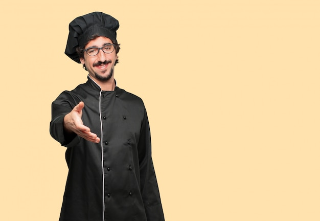 Young crazy man as a chef with a smiling, confident, proud, satisfied and friendly expression