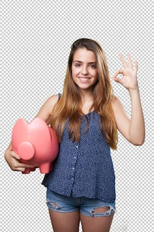 Young cute woman doing okay gesture holding a piggy bank