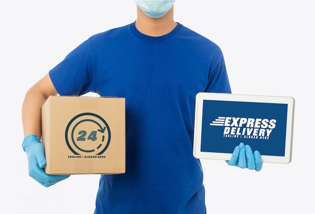 Молодой доставщик держит бумажную картонную коробку и планшетный компьютер макет