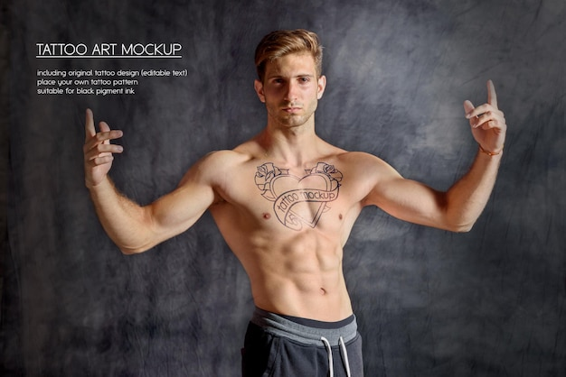 Young fitness man showing tattoo on his chest in a dark gym