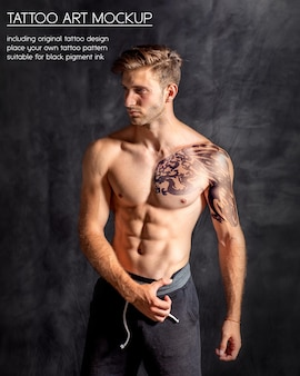 Молодой фитнес-мужчина показывает татуировку на груди и плече в темном тренажерном зале