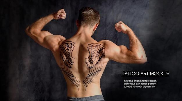 Молодой фитнес-мужчина показывает татуировку на спине в темном тренажерном зале