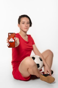 デジタルデバイスのモックアップを示す若いサッカー選手