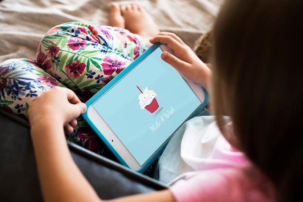 어린 소녀는 디지털 태블릿을 사용하고 있습니다