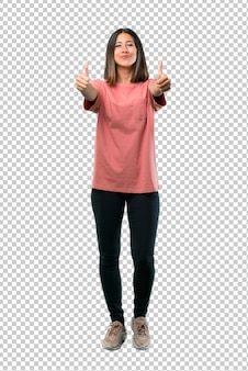 Young girl with pink shirt giving a thumbs up gesture with both hands and smiling