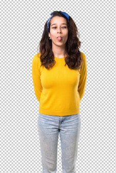 Young girl with yellow sweater and blue bandana on her head makes funny and crazy face emotion