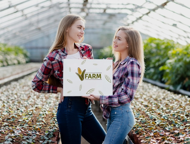 Молодые девушки с табличкой фермы