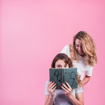 Young girls holding book cover mockup