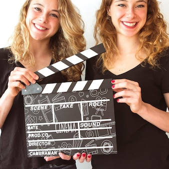 Young girls holding clapperboard mockup