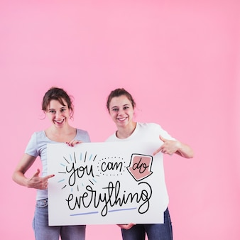 Young girls holding white board mockup